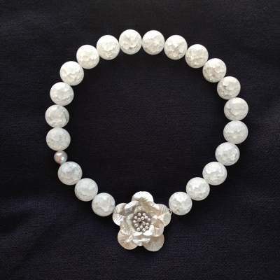 Mutiara: Kristal met parel en zilver bloemslot €325,-